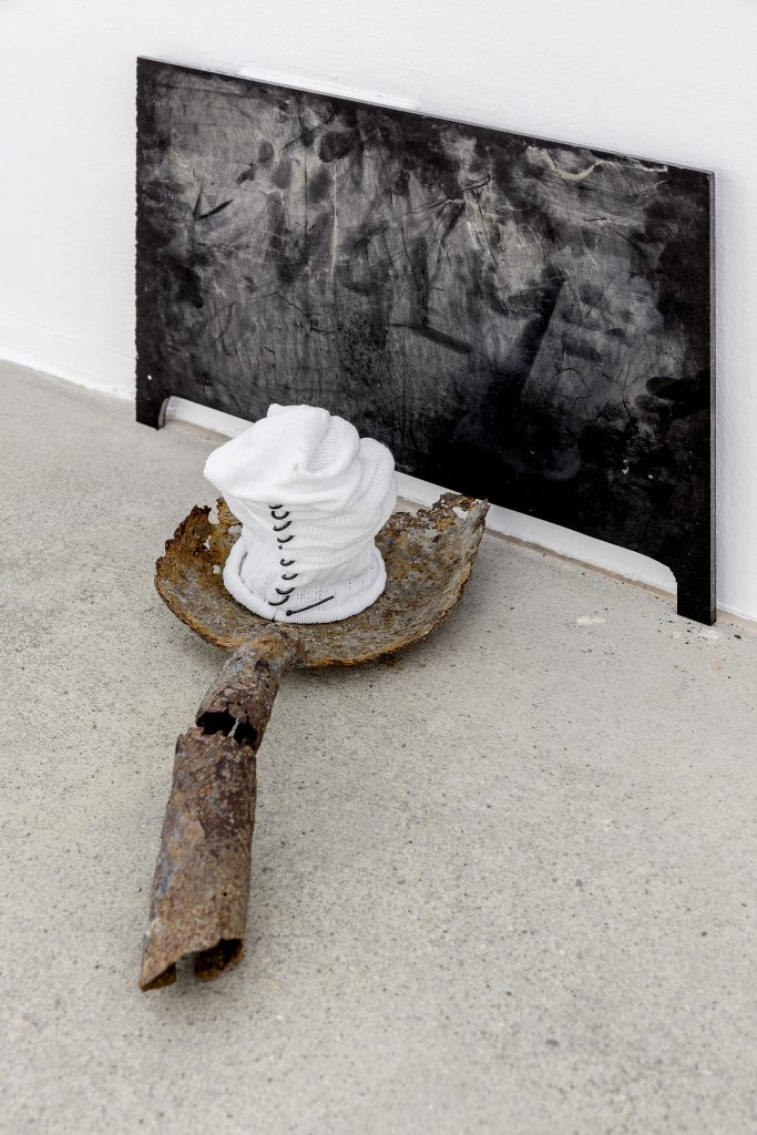 Sophie Jung, Mourning Fail (detail), 2017, Rusty wheel (cap), mourning veil, 3D printed penises, rusty shovel, tennis sock, plastic string, perspex, dust, dimensions variable. Photography: www.kunst-dokumentation.com. Courtesy: Sophie Tappeiner