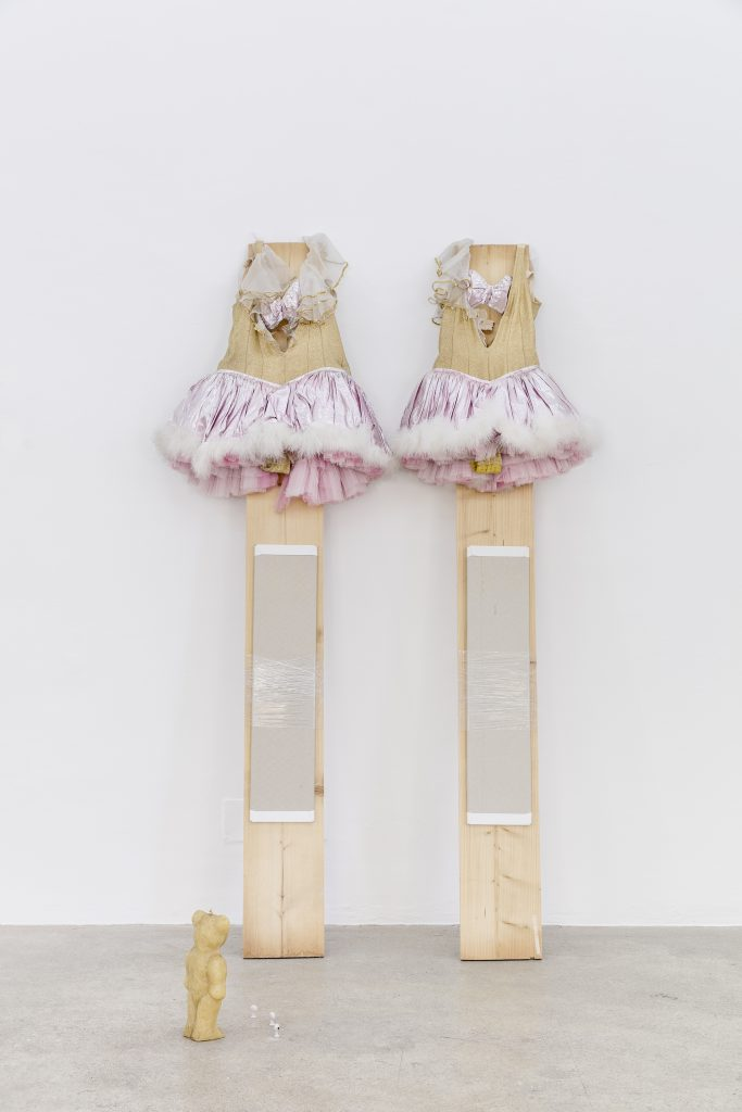 Sophie Jung, Clap Clap Clap, 2017, Ballerina dresses, fabric board, cling film, bed boards, bear candle, alien figures, dimensions variable. Photography: www.kunst-dokumentation.com. Courtesy: Sophie Tappeiner