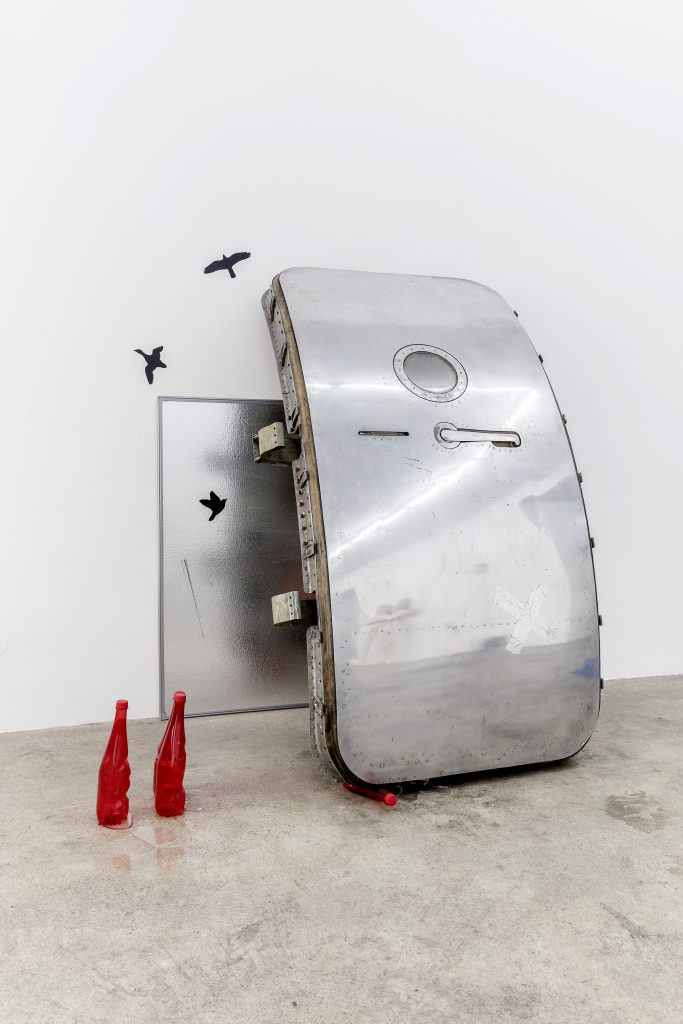 Sophie Jung, Tragedy Upon Tragedy, 2017. Airplane door, bird stickers, noteboard, plastic bottles, resin, metallic tape, photograph (artist's mother) same book in different editions (artist's father in law's collection) rusty bolt, packing foam, tar paint, dimensions variable. Photography: www.kunst-dokumentation.com. Courtesy: Sophie Tappeiner