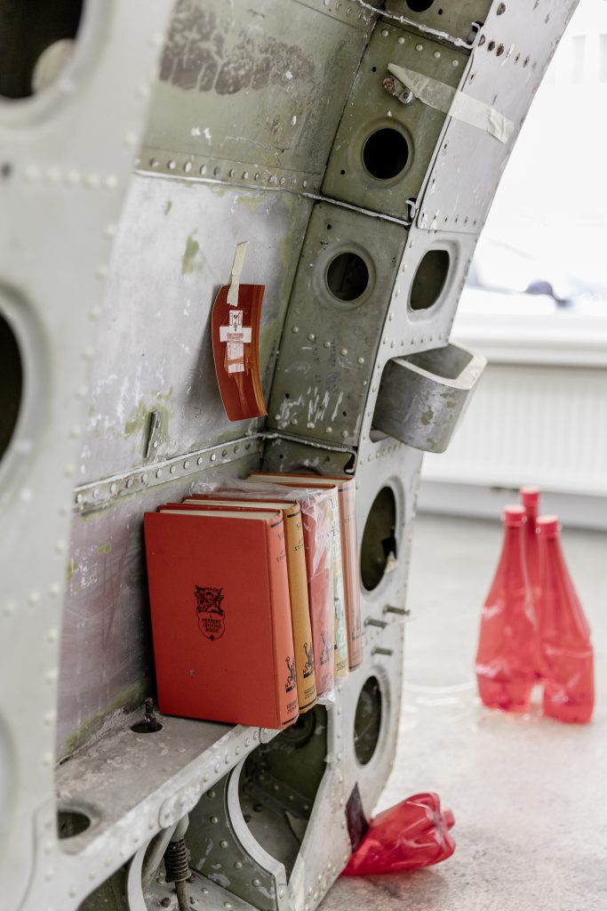 Sophie Jung, Tragedy Upon Tragedy (detail), 2017. Airplane door, bird stickers, noteboard, plastic bottles, resin, metallic tape, photograph (artist's mother) same book in different editions (artist's father in law's collection) rusty bolt, packing foam, tar paint, dimensions variable. Photography: www.kunst-dokumentation.com. Courtesy: Sophie Tappeiner